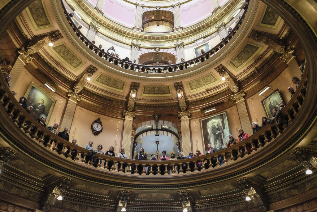 In this Tuesday, Dec. 4, 2018, photo, people gather to protest in the Capitol Rotunda in Lansing, Mich. The incoming Democratic governor of Wisconsin