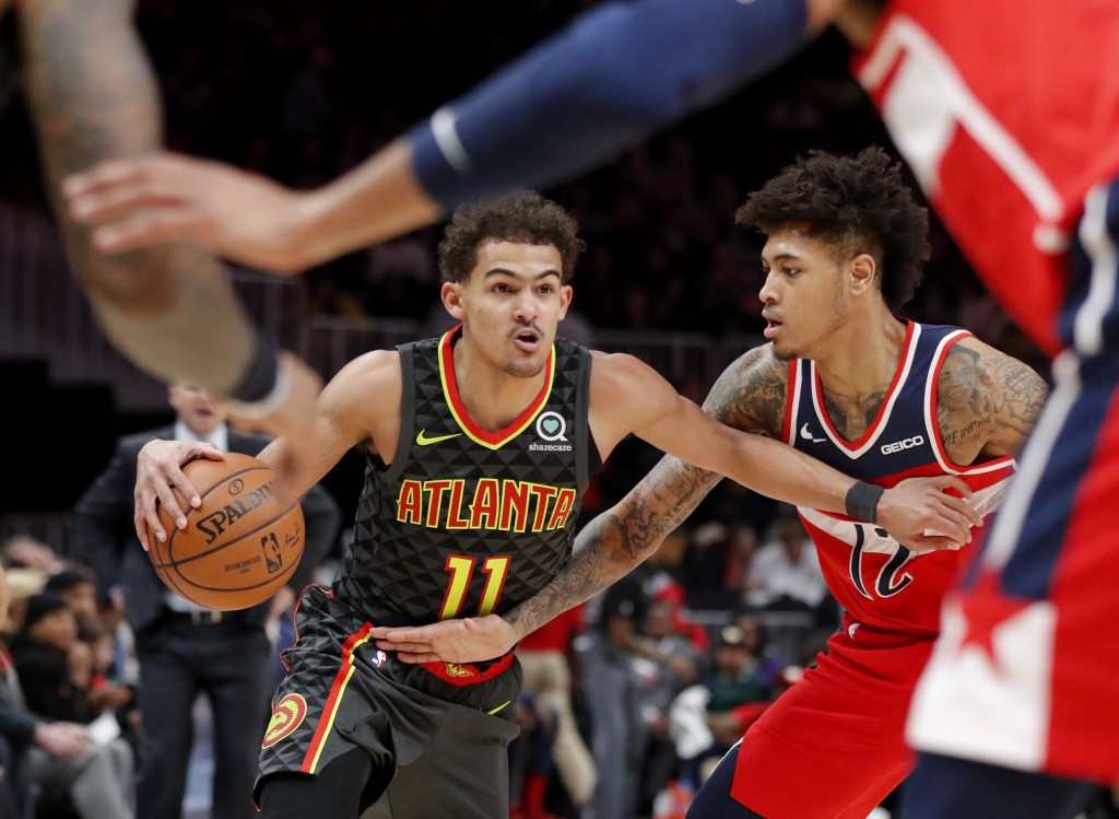 Atlanta Hawks guard Trae Young (11) drives as Washington Wizards forward Kelly Oubre Jr. (12) defends during the first half of an NBA basketball game