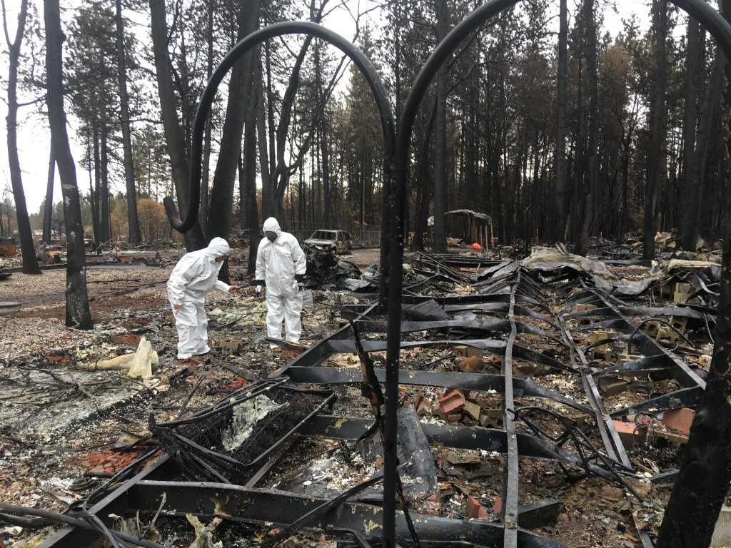 Jerry and Joyce McLean, wearing hazmat suits, look for sentimental items sifting through the remains of their home Wednesday, Dec. 5, 2018, in Paradis
