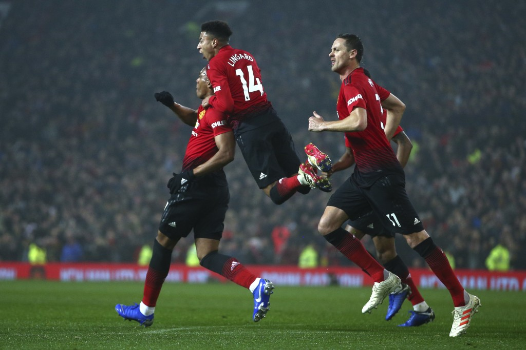 Manchester United's midfielder Jesse Lingard, center, jumps on the shoulders of teammate Anthony Martial who scored his side's first goal during the E
