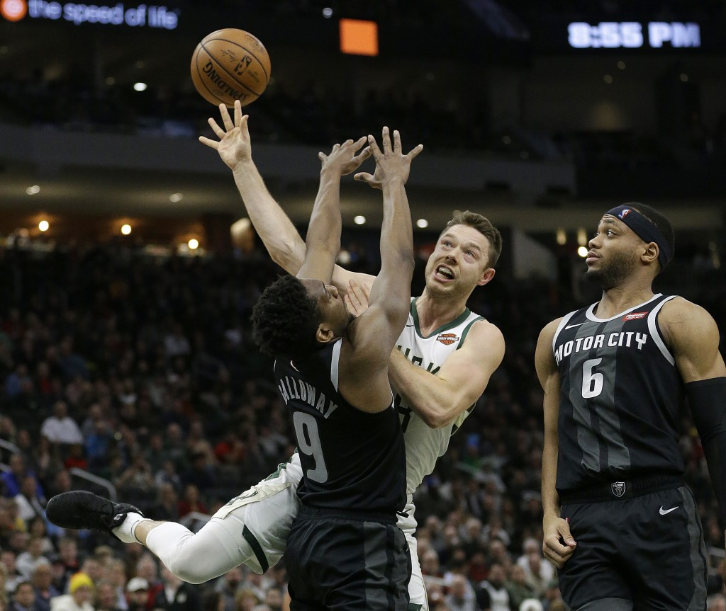 Milwaukee Bucks' Matthew Dellavedova, middle, is, fouled between Detroit Pistons' Langston Galloway (9) and Bruce Brown (6) during the second half of