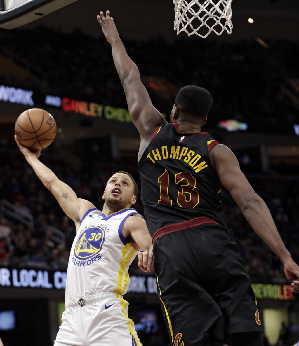Golden State Warriors' Stephen Curry, left, drives to the basket against Cleveland Cavaliers' Tristan Thompson in the second half of an NBA basketball