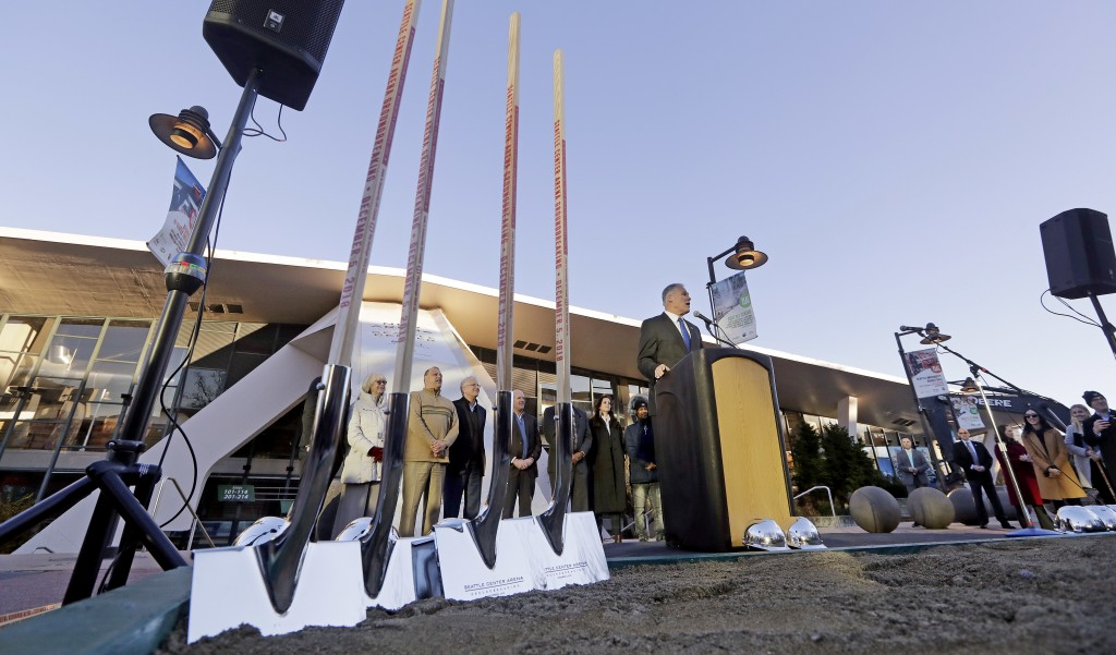 Gov. Jay Inslee speaks as engraved shovels stand at the ready before a ceremonial groundbreaking of a renovation of the arena behind at Seattle Center