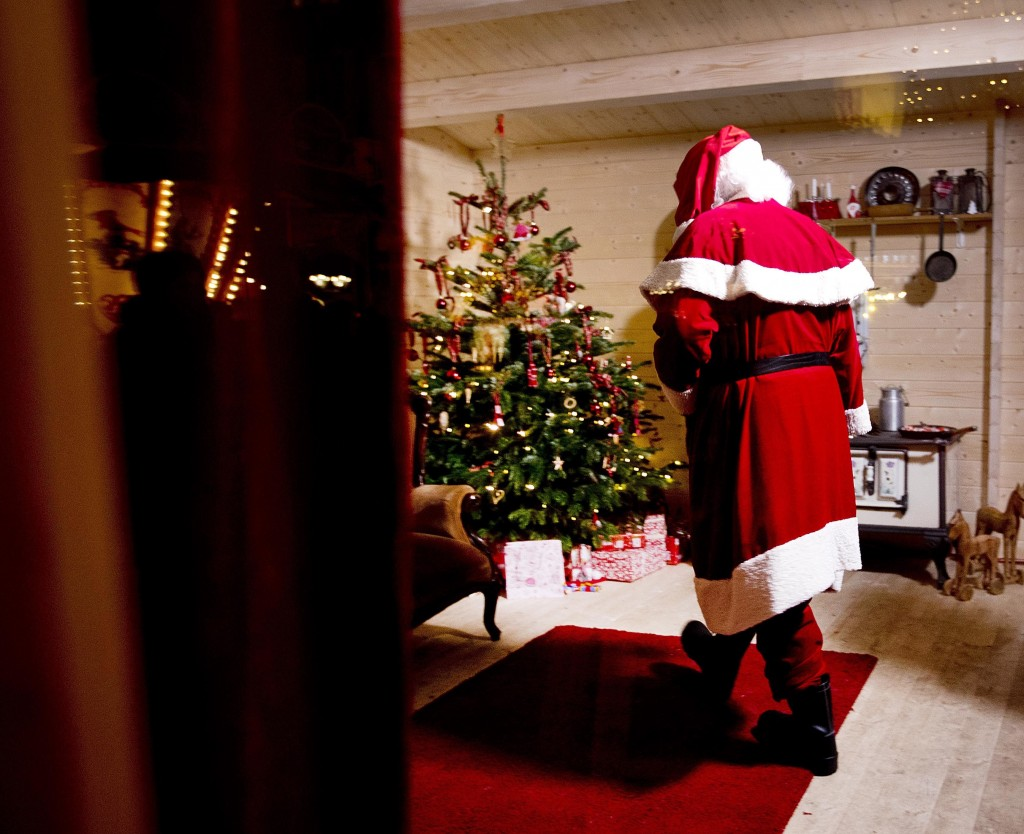 In this Tuesday, Dec. 4, 2018 photo a man dressed as Santa Claus walks up and down in a small house waiting for customers to be photographed with at t