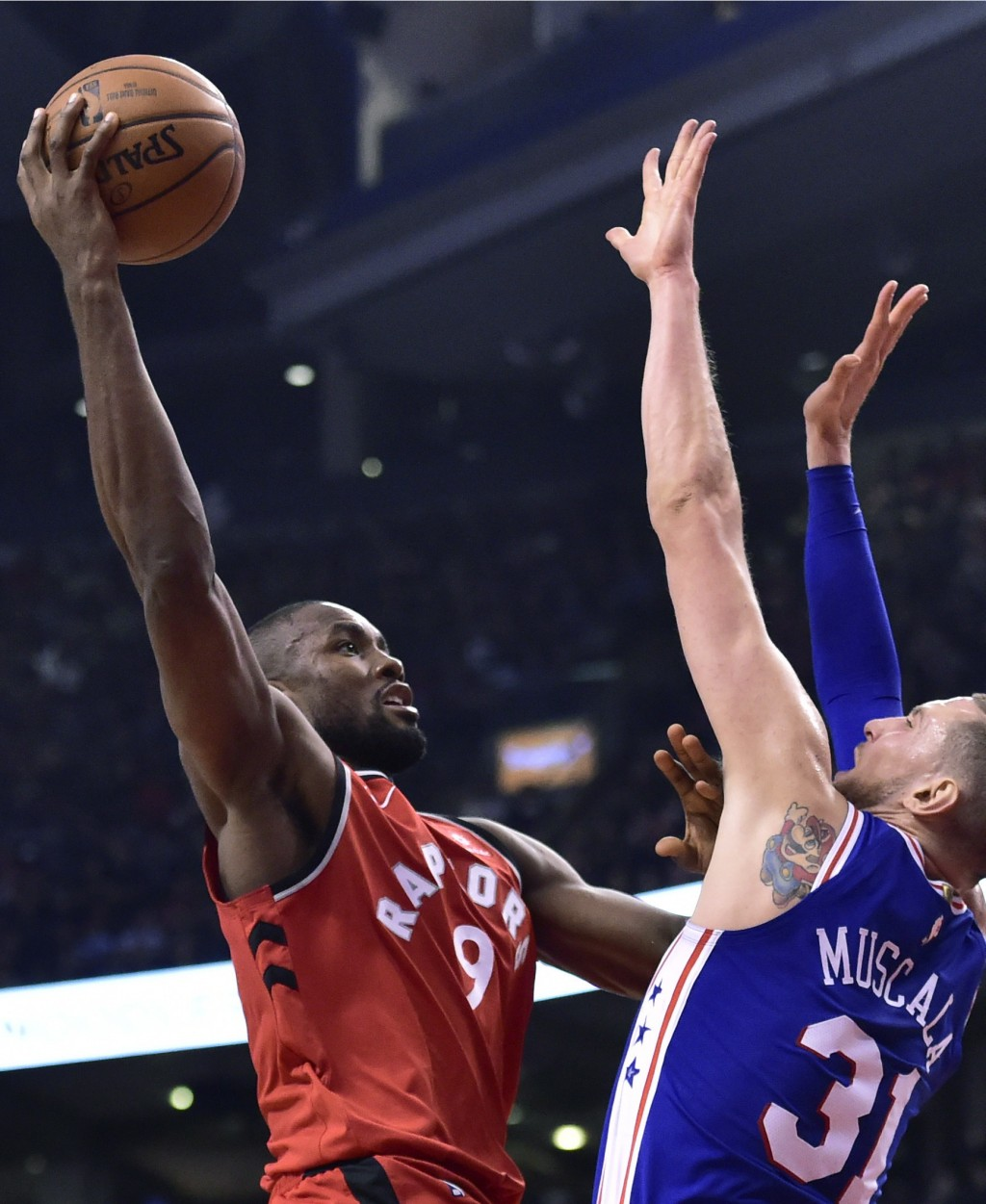 Toronto Raptors forward Serge Ibaka (9) shoots over Philadelphia 76ers forward Mike Muscala (31) during the first half of an NBA basketball game, Wedn