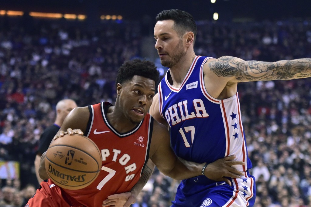 Toronto Raptors guard Kyle Lowry (7) drives around Philadelphia 76ers guard JJ Redick (17) during the first half of an NBA basketball game, Wednesday,