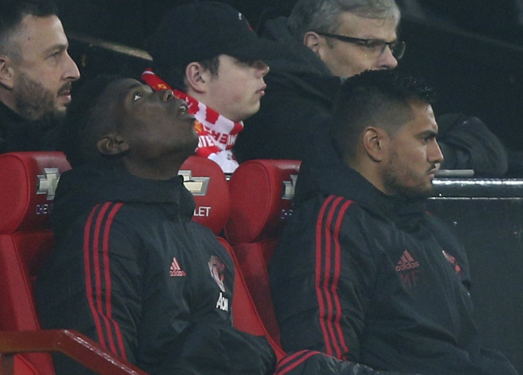 Arsenal's Paul Pogba, left, sits on the substitute bench during the English Premier League soccer match between Manchester United and Arsenal at Old T