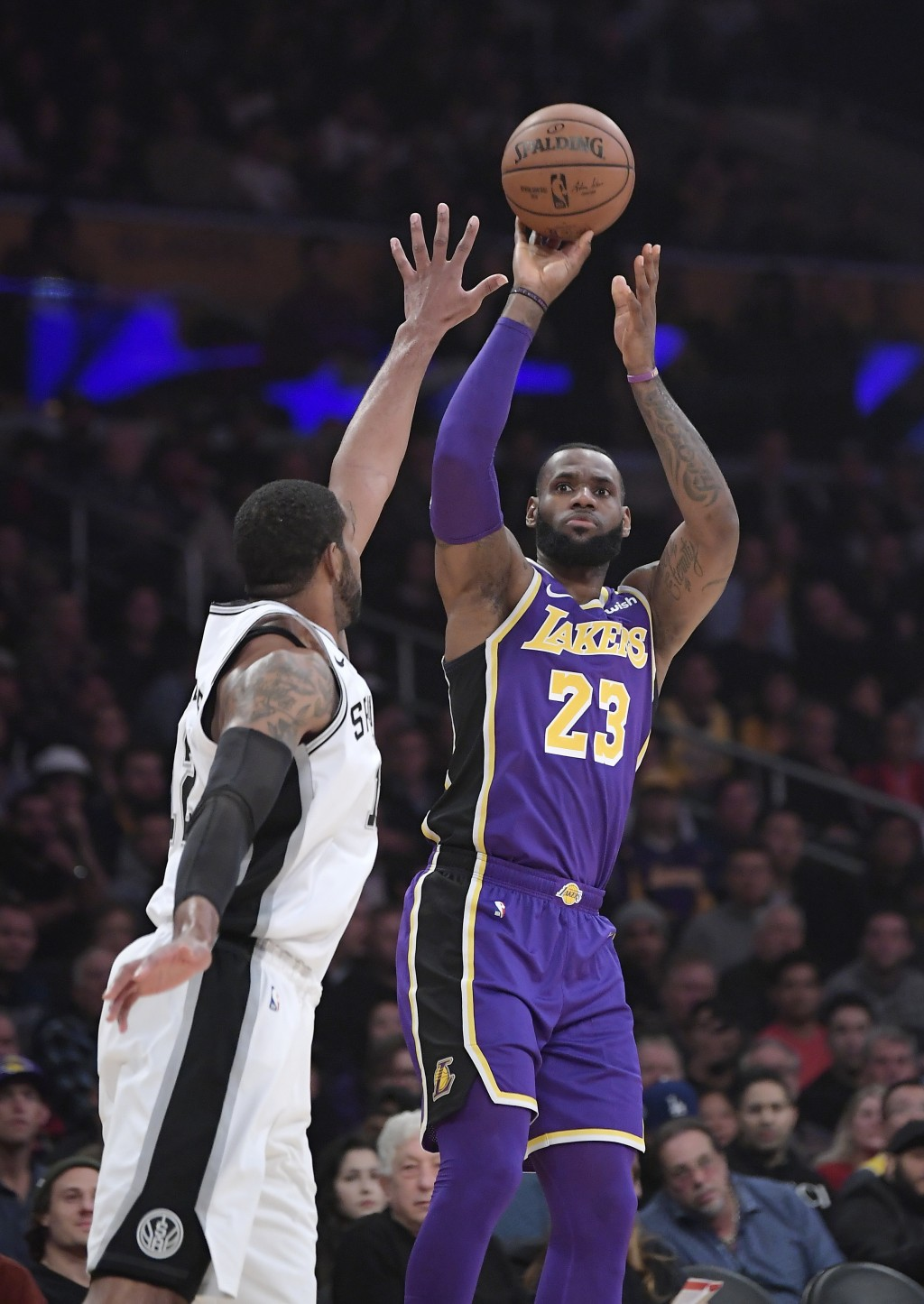 Los Angeles Lakers forward LeBron James, right, shoots as San Antonio Spurs forward LaMarcus Aldridge defends during the first half of an NBA basketba