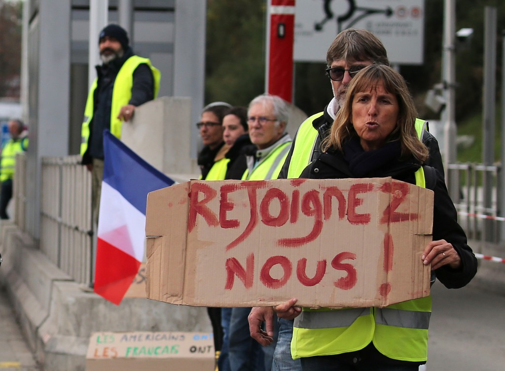"""A demonstrator holds a placard reading """" Join us"""" as they stand by toll gates on a motorway at Biarritz southwestern France, Wednesday, Dec.5, 2018. T"""