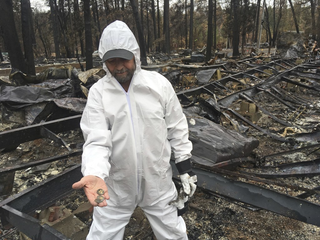 Jerry McLean, wearing a hazmat suit, holds out some old coins that he found in the remains of his home Wednesday, Dec. 5, 2018, in Paradise Calif. Som
