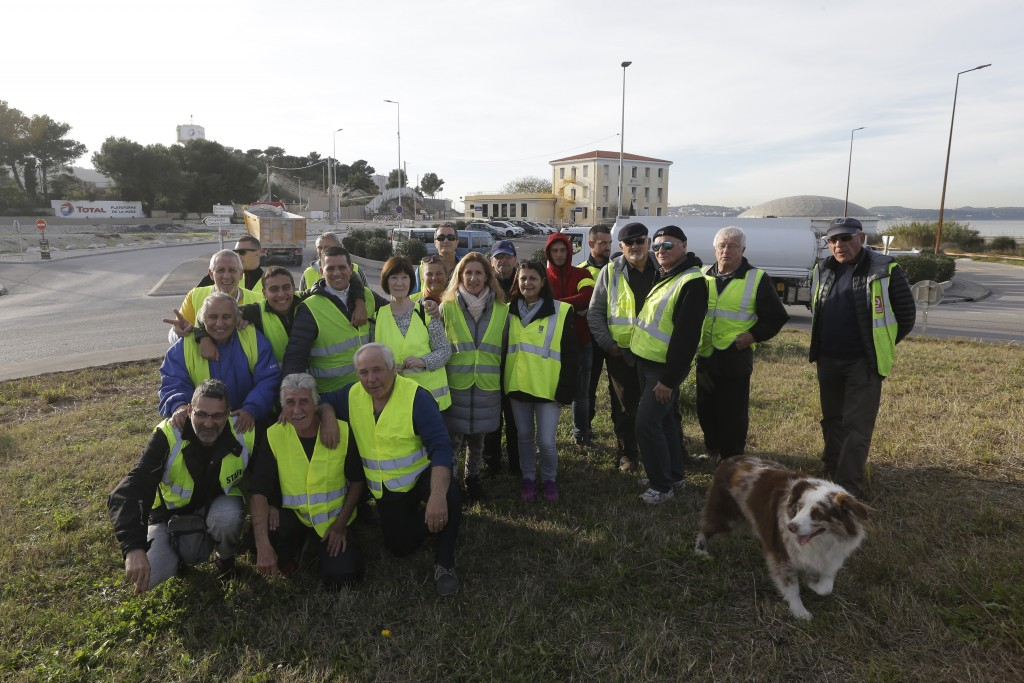 A group of demonstrators wearing their yellow vest pose on an occupied traffic circle, Wednesday, Dec. 5, 2018 outside La Mede oil refinery, near Mart