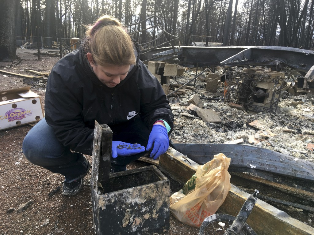 In this photo taken Wednesday, Dec. 5, 2018 Jennifer Christensen sorts through items found in a safe at the remains of her home in Paradise, Calif. Ch