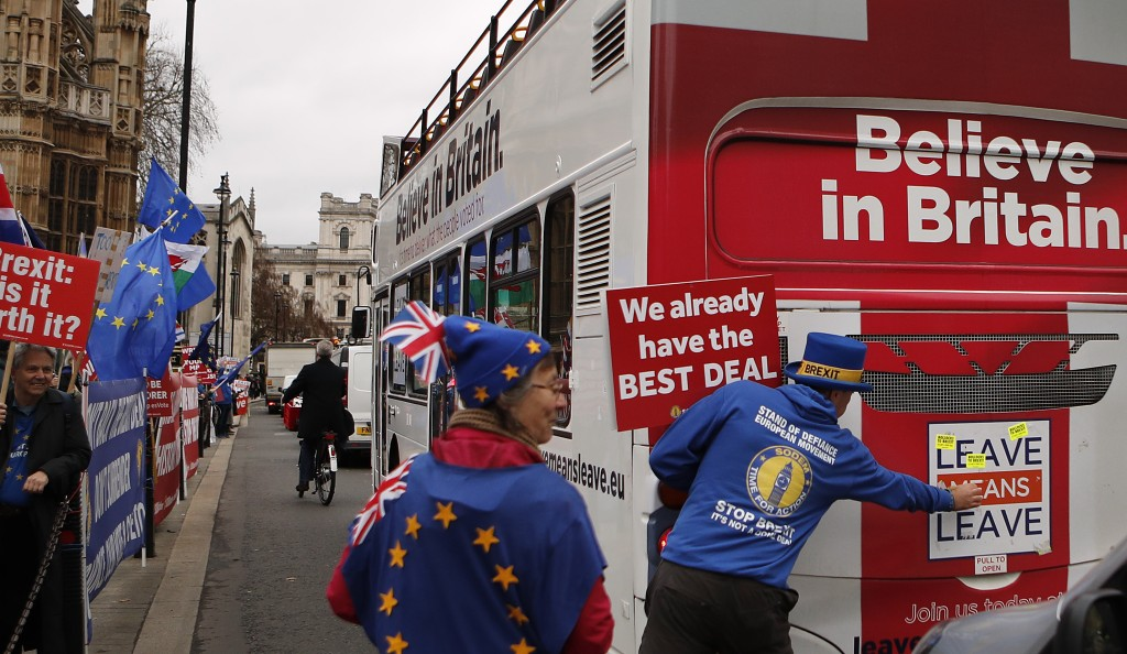 Anti Brexit demonstrators put stickers on a bus during a protest outside the Houses of Parliament in London Thursday Dec. 6, 2018.  Britain's Prime Mi