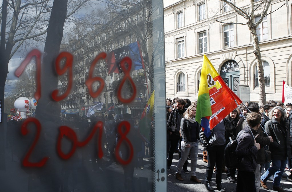 FILE - In this April 10, 2018 file photo, students demonstrate past a board tagged in reference to May 1968, in Paris. Fifty years ago, students in th