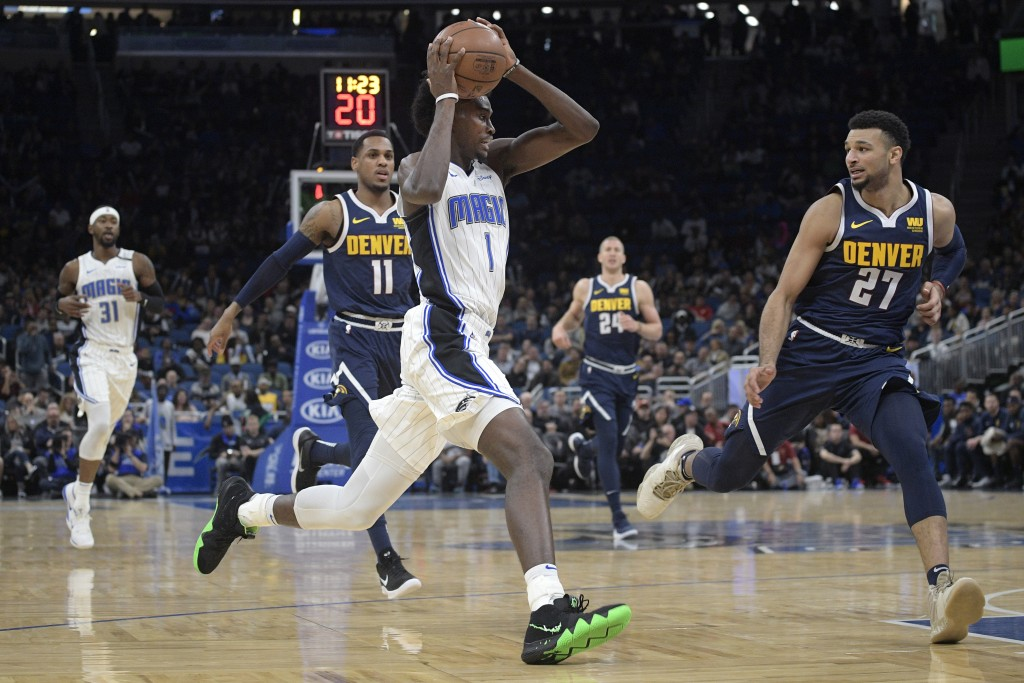 Orlando Magic forward Jonathan Isaac (1) drives to the basket in front of Denver Nuggets guard Monte Morris (11) and guard Jamal Murray (27) during th