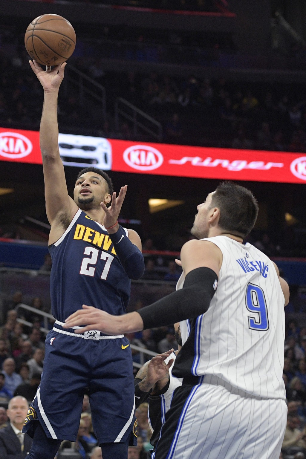 Denver Nuggets guard Jamal Murray (27) goes up for a shot in front of Orlando Magic center Nikola Vucevic (9) during the first half of an NBA basketba