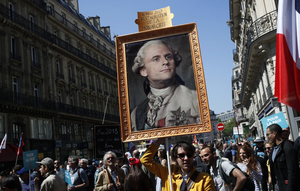 FILE - In this Saturday, May 5, 2018 file picture a protester carries a picture of French President Emmanuel Macron depicted as King Louis XVI during