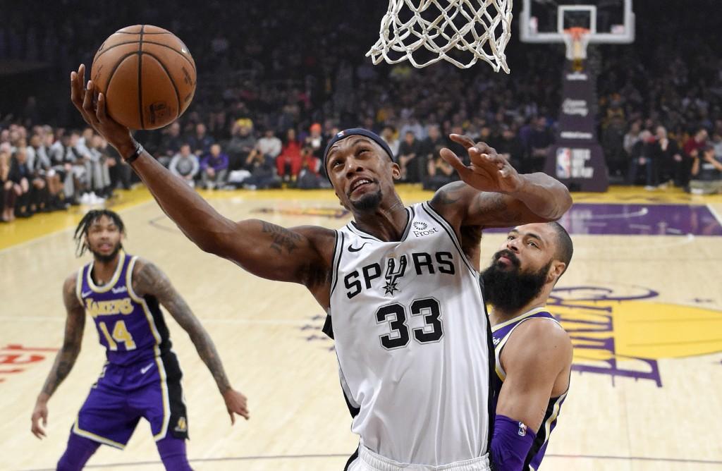 San Antonio Spurs forward Dante Cunningham, center, shoots as Los Angeles Lakers forward Brandon Ingram, left, and center Tyson Chandler defend during