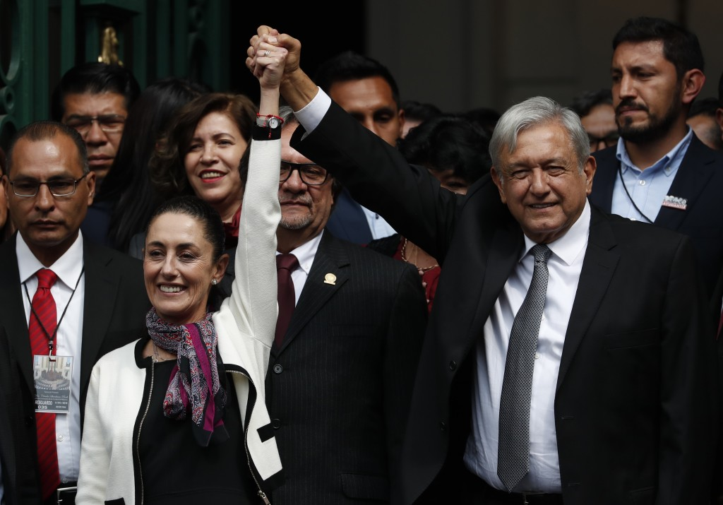 The first elected female mayor of Mexico City Claudia Sheinbaum and President Andres Manuel Lopez Obrador lift their arms in unison after she was swor
