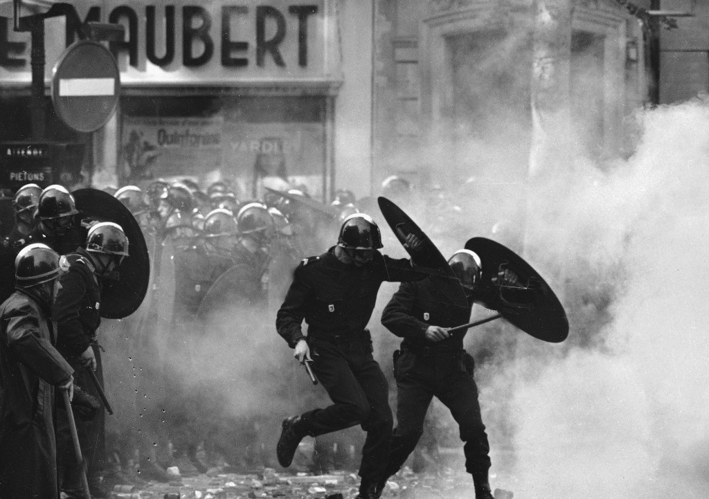 FILE - Anti-riot police charge through the streets of Paris during violent student demonstrations on May. 6, 1968. There are parallels for unpopular F