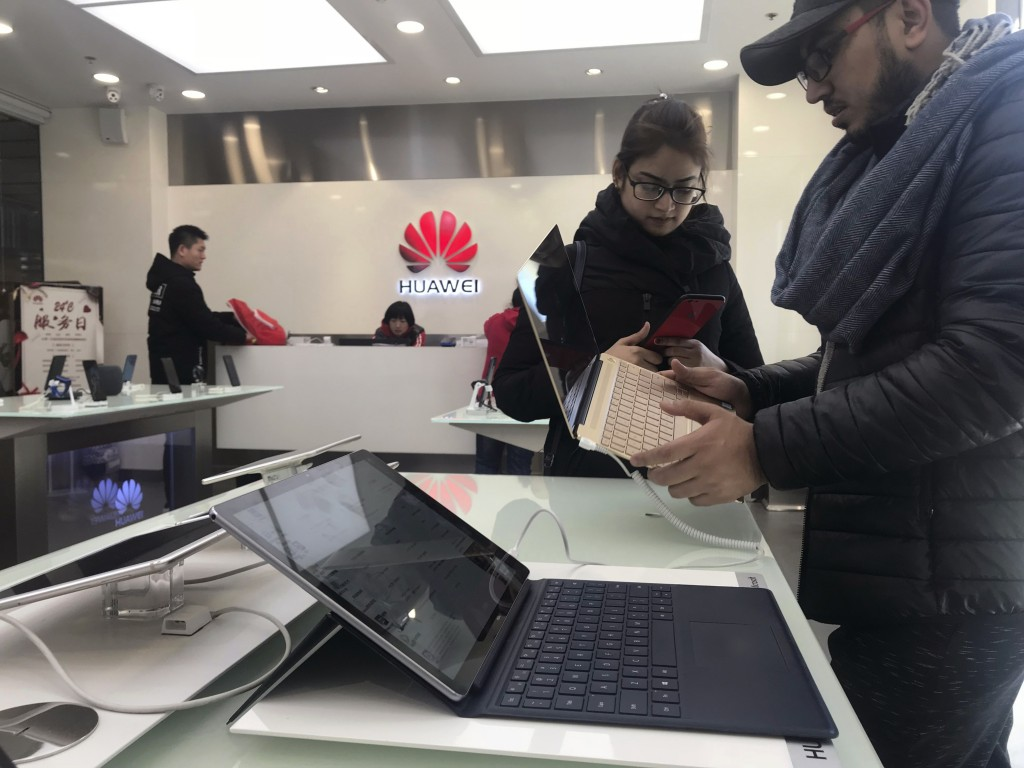 Foreigners look at a Huawei computer at a Huawei store in Beijing, China, Thursday, Dec. 6, 2018. Canadian authorities said Wednesday that they have a