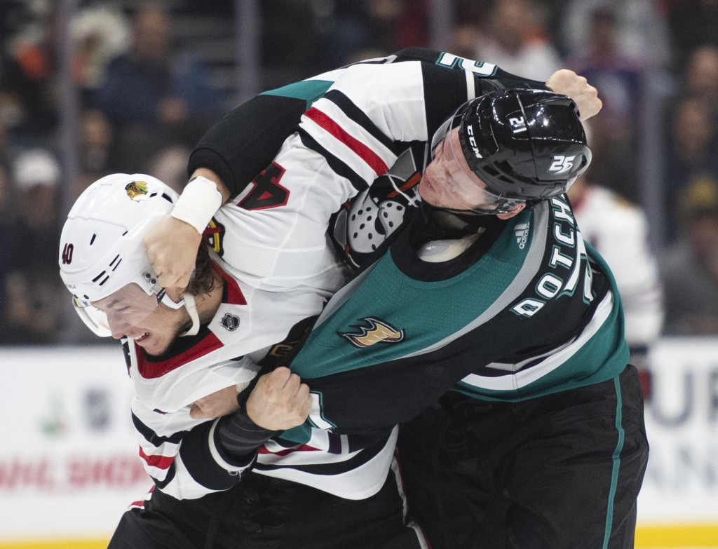 Anaheim Ducks defenseman Jake Dotchin, right, and Chicago Blackhawks right wing John Hayden fight in the first period of an NHL hockey game in Anaheim
