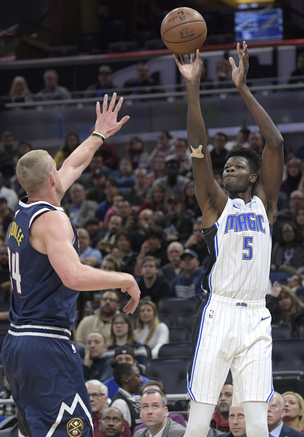 Orlando Magic center Mo Bamba (5) goes up for a shot in front of Denver Nuggets forward Mason Plumlee (24) during the first half of an NBA basketball