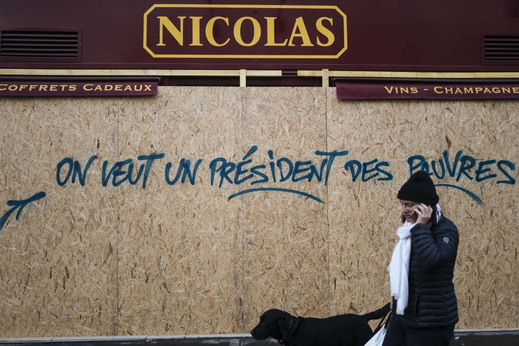 FILE - In this Sunday, Dec. 2, 2018 file picture, a woman walks past a graffiti on a boarded up wine shop reading 'We want a president for the poor',