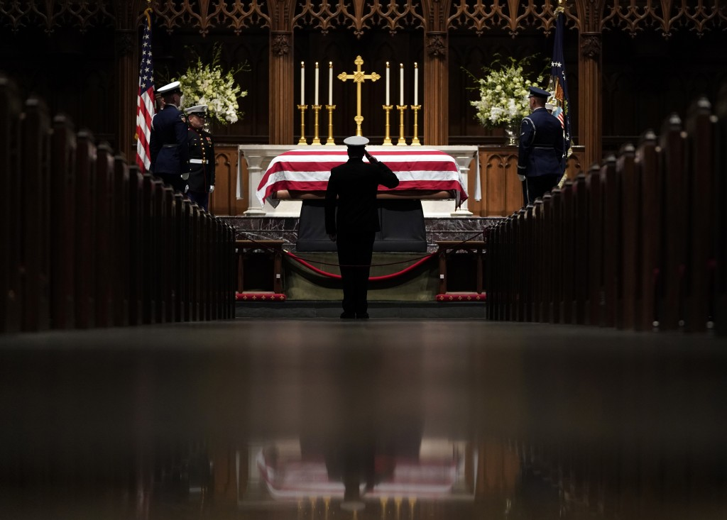 People pay their respects as the flag-draped casket of former President George H.W. Bush lies in repose at St. Martin's Episcopal Church Wednesday, De