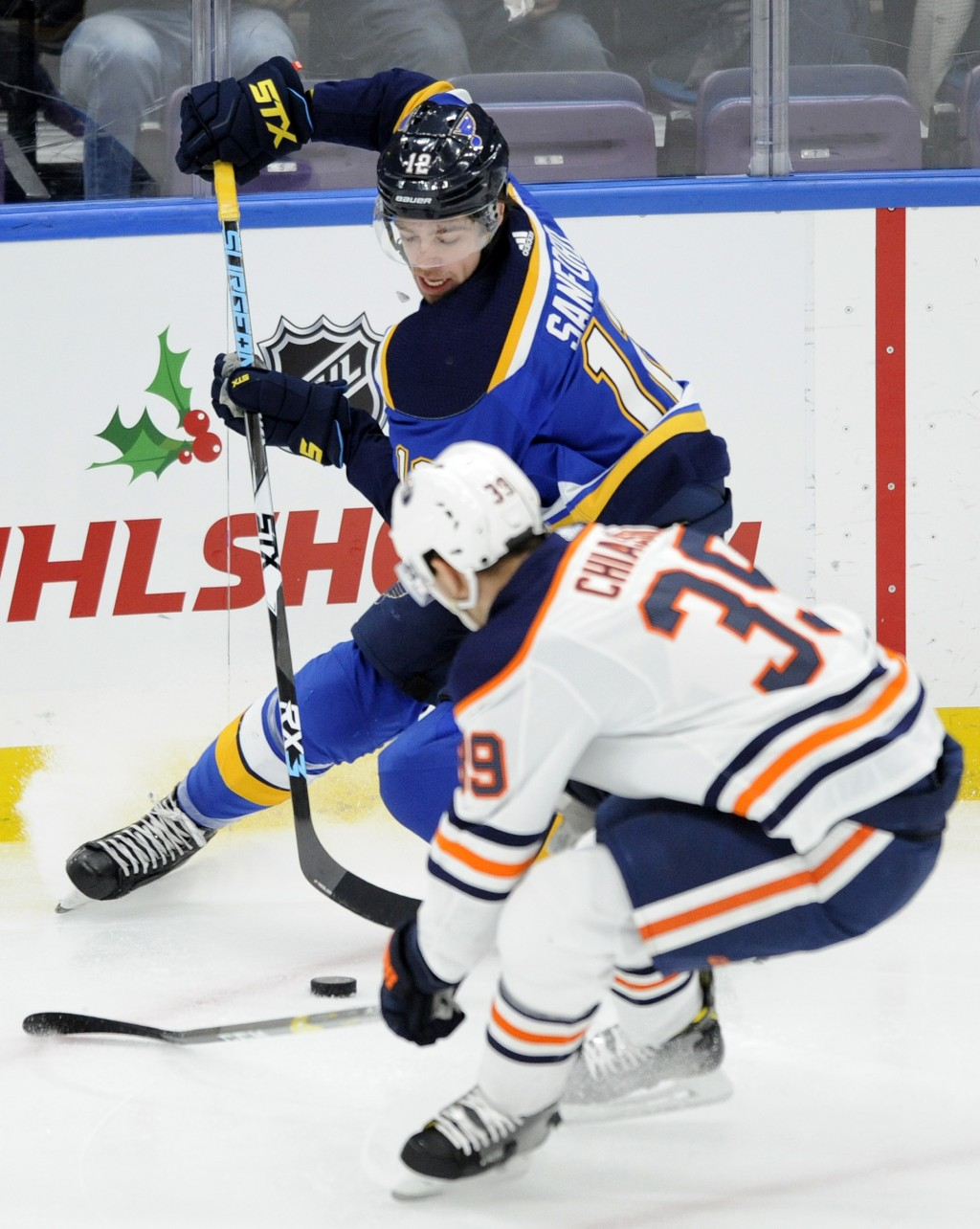 St. Louis Blues' Zach Sanford (12) reaches for the puck against Edmonton Oilers' Alex Chiasson (39) during the first period of an NHL hockey game, Wed