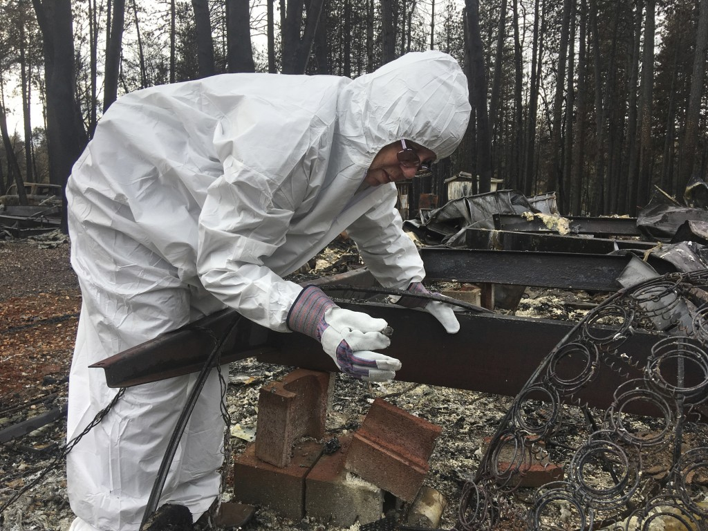 Joyce McLean, wearing a hazmat suit, looks through the remains of her home Wednesday, Dec. 5, 2018, in Paradise Calif. Some residents of a California