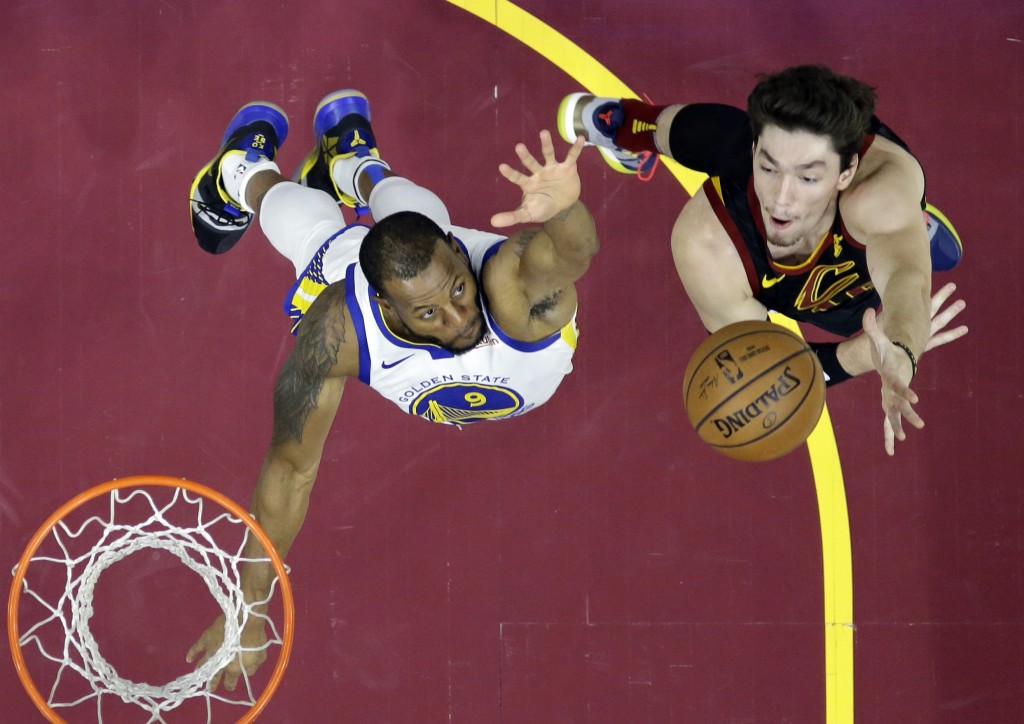 Cleveland Cavaliers' Cedi Osman, right, from Turkey, shoots over Golden State Warriors' Andre Iguodala in the first half of an NBA basketball game, We