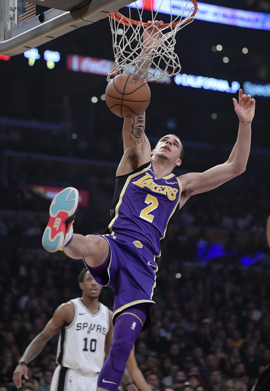Los Angeles Lakers guard Lonzo Ball, right, dunks as San Antonio Spurs guard DeMar DeRozan watches during the first half of an NBA basketball game, We