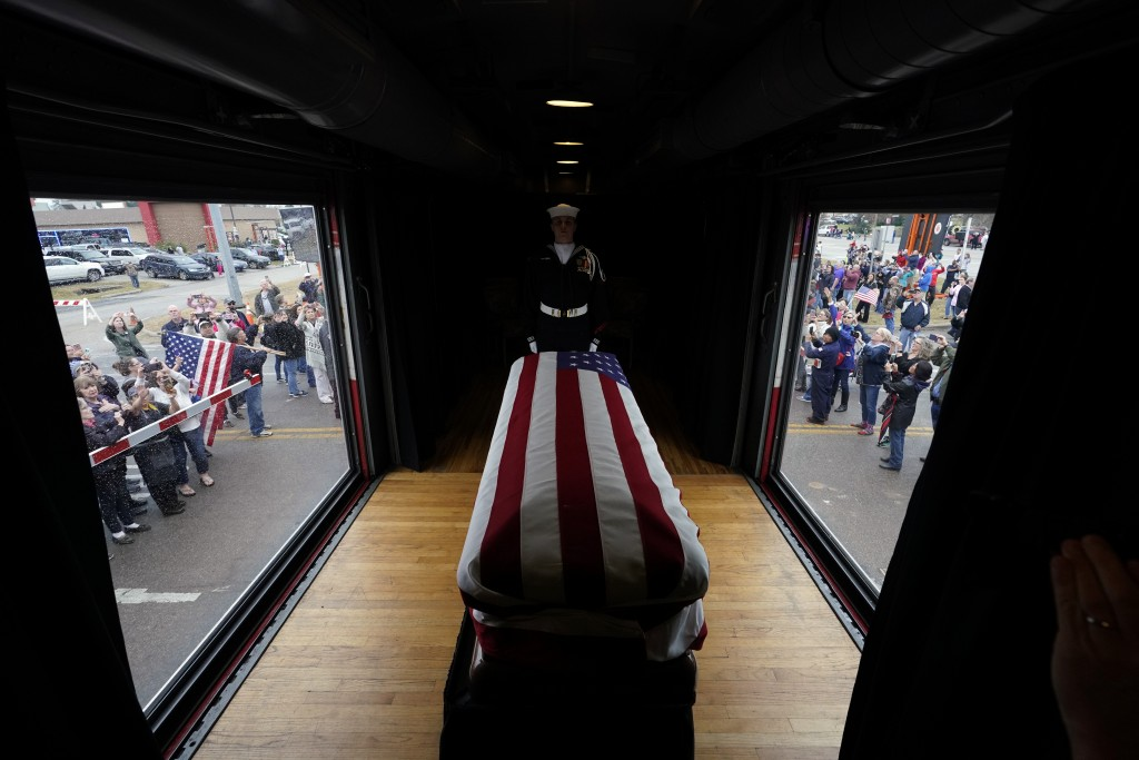 The flag-draped casket of former President George H.W. Bush passes through Magnolia, Texas, Thursday, Dec. 6, 2018, along the train route from Spring