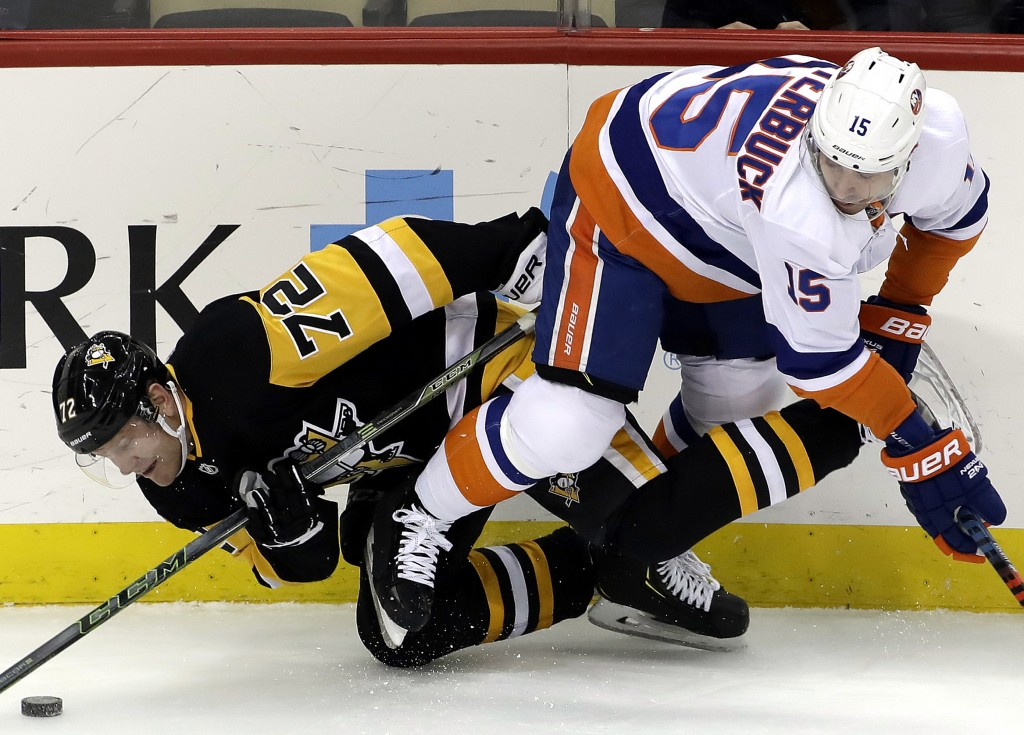 Pittsburgh Penguins' Patric Hornqvist (72) collides with New York Islanders' Cal Clutterbuck (15) during the first period of an NHL hockey game in Pit