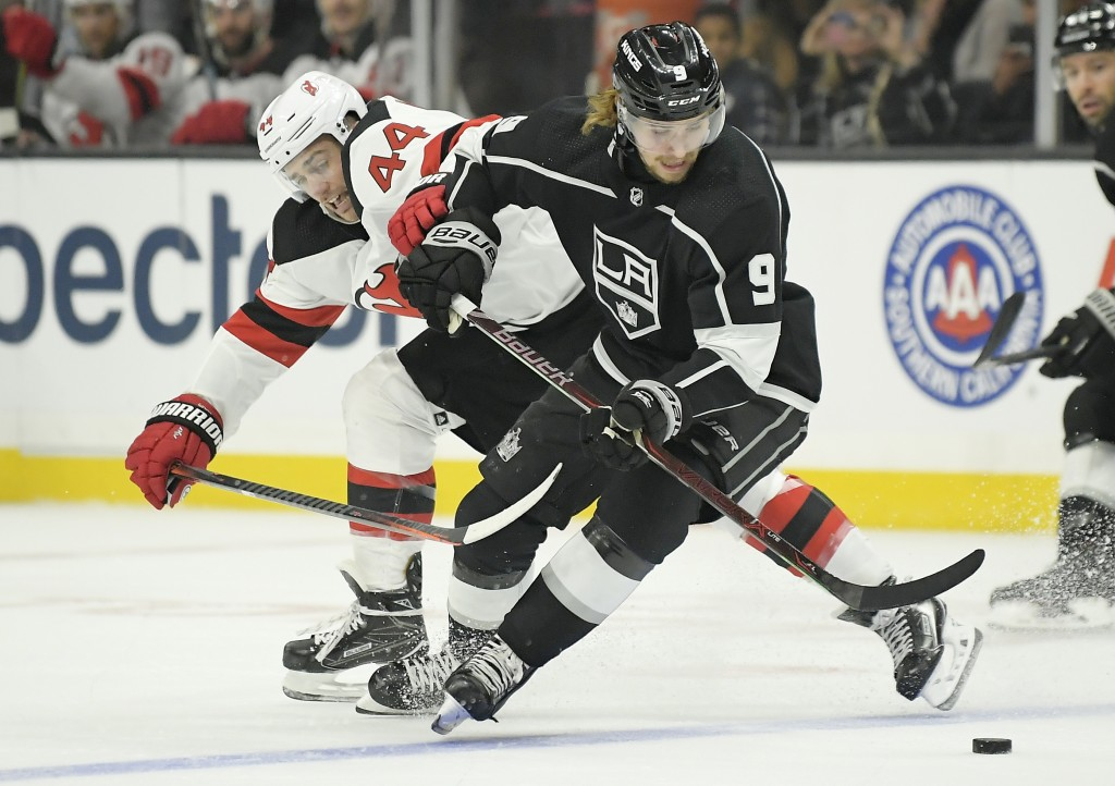 New Jersey Devils left wing Miles Wood, left, reaches in on Los Angeles Kings center Adrian Kempe, of Sweden, during the first period of an NHL hockey