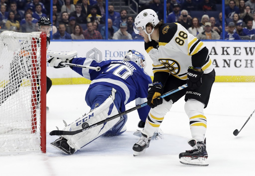 Tampa Bay Lightning goaltender Louis Domingue (70) makes a pad save on a shot by Boston Bruins right wing David Pastrnak (88) during the first period