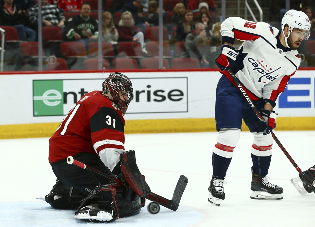 Arizona Coyotes goaltender Adin Hill (31) makes a save on a deflection from Washington Capitals center Chandler Stephenson (18) during the first perio