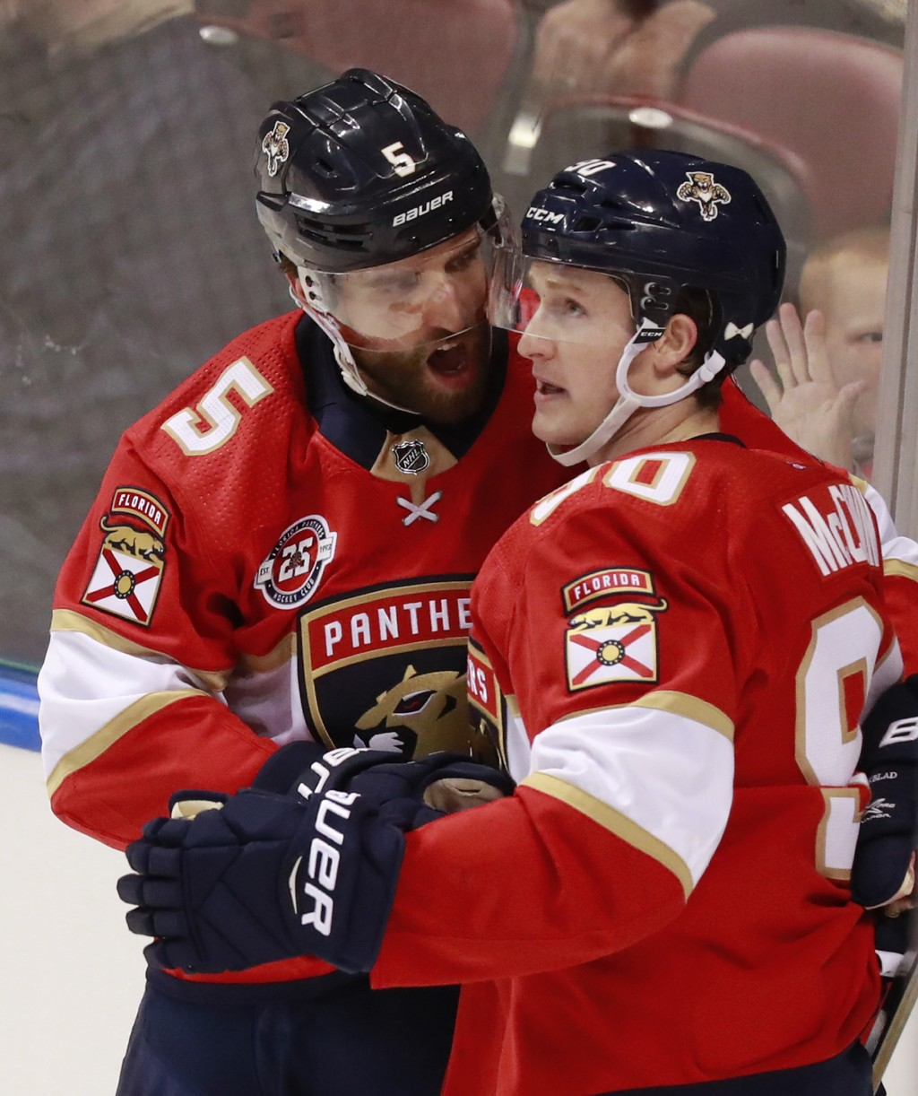 Florida Panthers defenseman Aaron Ekblad (5) celebrates with center Jared McCann (90) after scoring a goal during the second period of an NHL hockey g