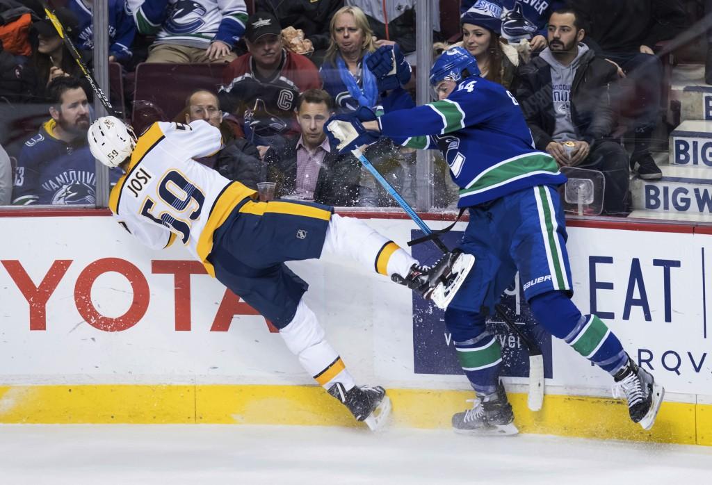 Vancouver Canucks' Erik Gudbranson, right, checks ...