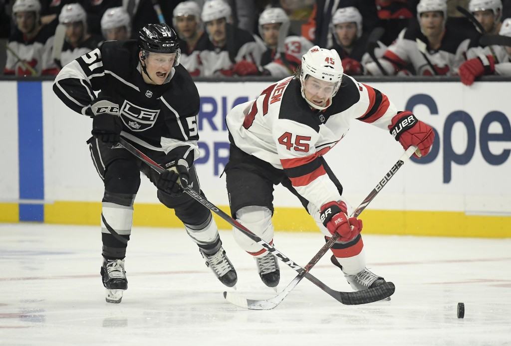 Los Angeles Kings left wing Austin Wagner, left, and New Jersey Devils defenseman Sami Vatanen, of Finland, race for the puck during the second period
