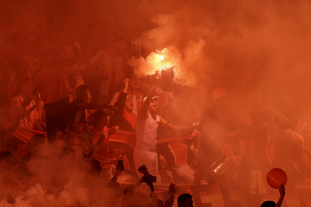 A Colombia Junior soccer fan holds up a burning flare as fans get revved before the start of the Copa Sudamericana first leg final match against Brazi