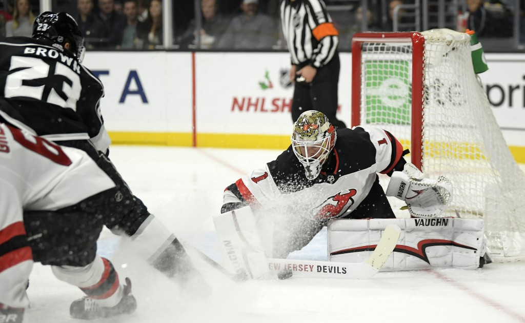 Los Angeles Kings right wing Dustin Brown, left, tries to get a shot past New Jersey Devils goaltender Keith Kinkaid during the second period of an NH