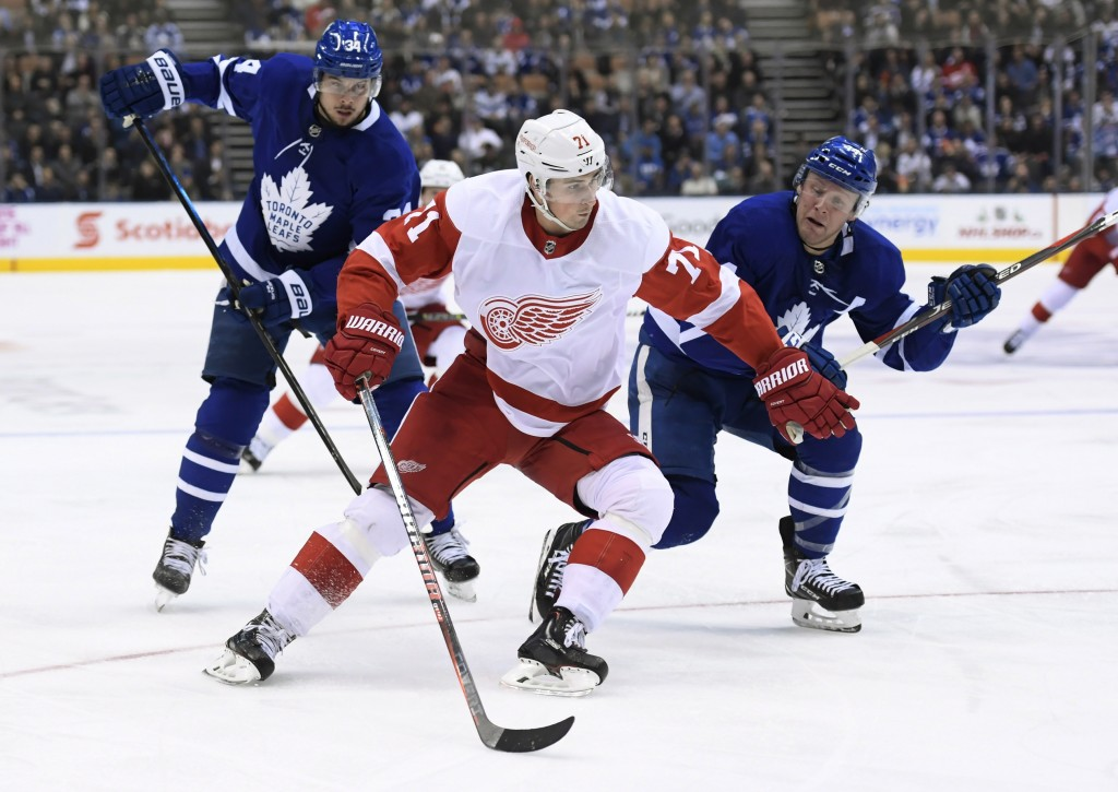 Detroit Red Wings center Dylan Larkin (71) moves past Toronto Maple Leafs defenseman Morgan Rielly (44) as Maple Leafs center Auston Matthews (34) wat