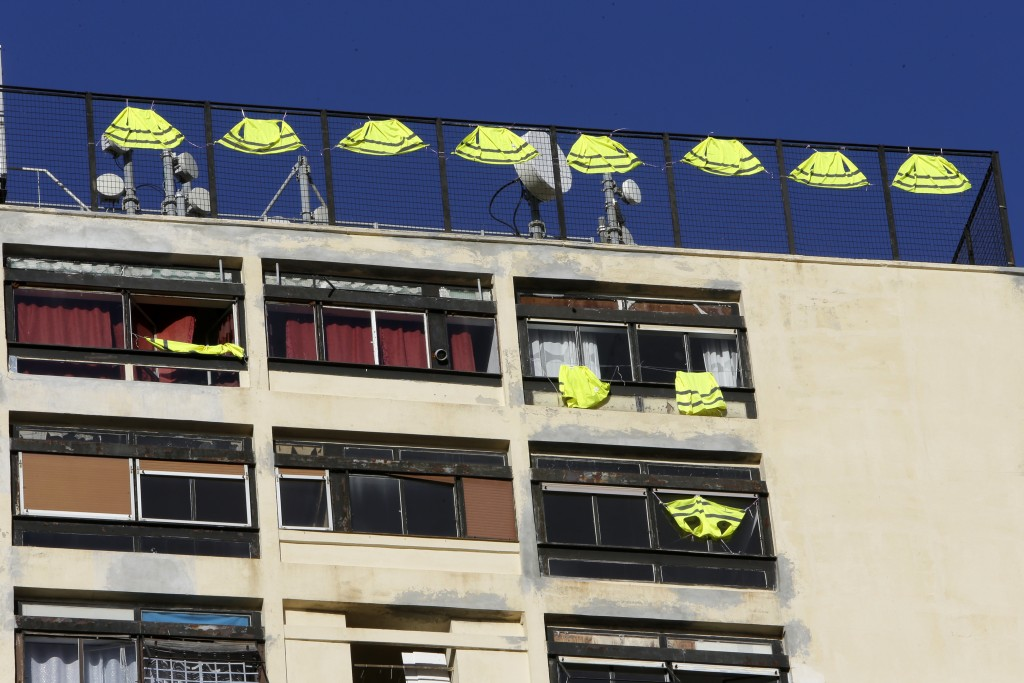 Yellow vests hang on the rooftop of an apartment building Friday, Dec. 7, 2018 in Marseille, southern France. Across the country, France is mobilizing