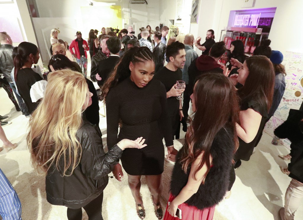 In this, Wednesday, Dec. 5, 2018 photo, tennis player Serena Williams, center, mingles with guests during the launch of her first pop-up shop at the F