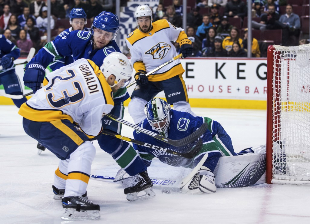 Nashville Predators' Rocco Grimaldi (23) is stopped by Vancouver Canucks goalie Jacob Markstrom, right, of Sweden, as Derrick Pouliot (5) defends duri