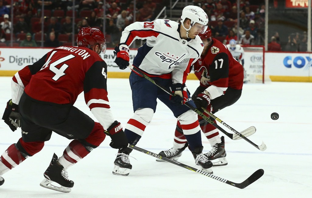 Washington Capitals center Lars Eller (20) tries to control the puck between Arizona Coyotes defenseman Kevin Connauton (44) and center Alex Galchenyu