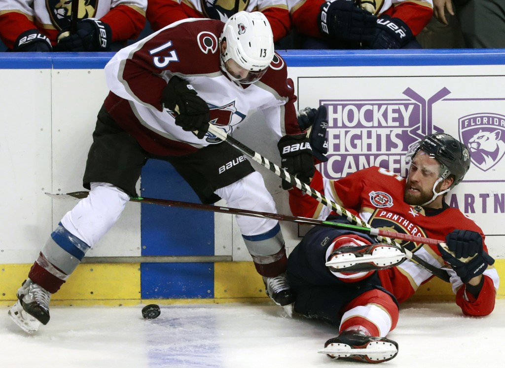 Colorado Avalanche center Alexander Kerfoot (13) and Florida Panthers defenseman Aaron Ekblad battle for the puck during the third period of an NHL ho