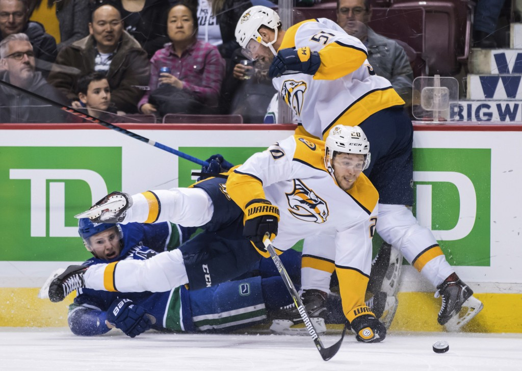 Nashville Predators' Miikka Salomaki, front, of Finland, falls over Vancouver Canucks' Troy Stecher, left, who was tripped by Nashville's Austin Watso